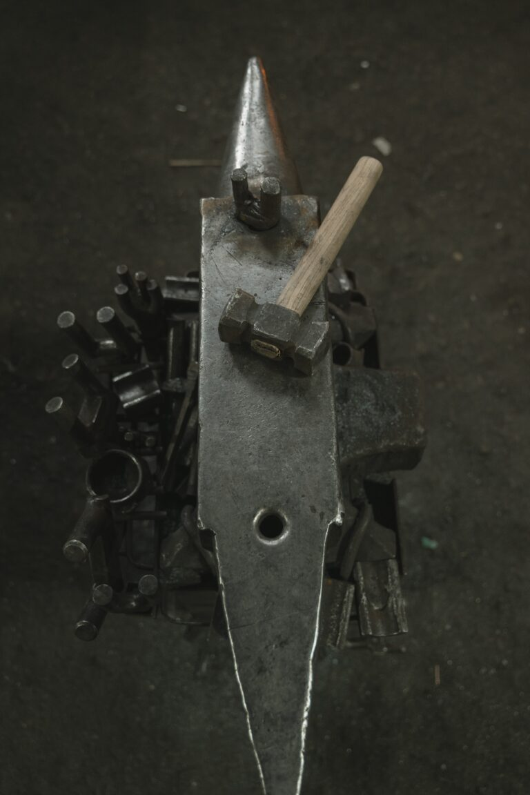 vertical photo of hammer laying on anvil